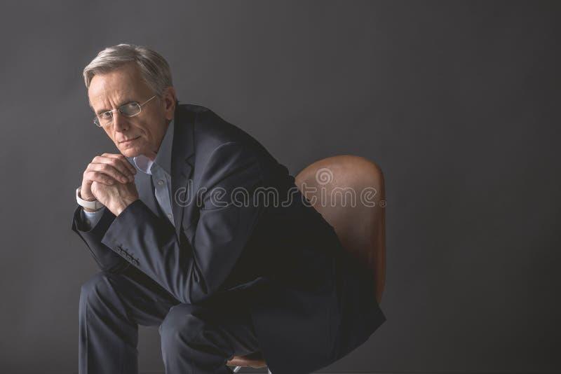 位于椅子的沉思老商人 免版税库存照片