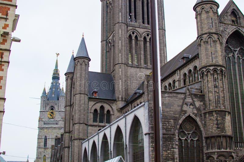 位于欧洲比利时根特的圣尼古拉斯教堂Sint-Niklaaskerk的门面,背景是Belfry Het Belfort 免版税库存照片