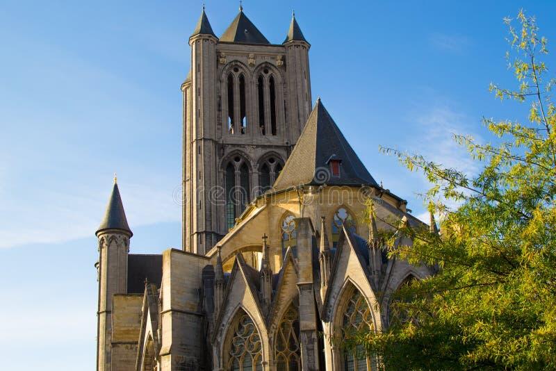 位于比利时根特的圣尼古拉斯教堂正面,在阳光明媚的阳光下,前面有绿树 库存图片