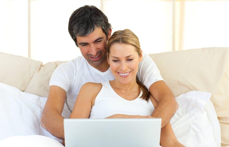 位于河床夫妇倾心的膝上型计算机使&# 免版税库存照片