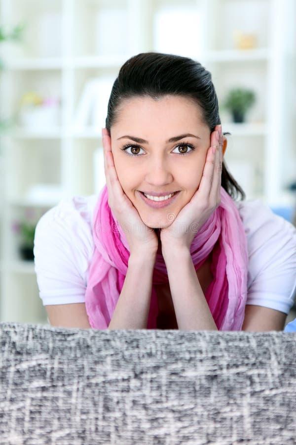 位于的微笑的女孩在沙发 库存图片