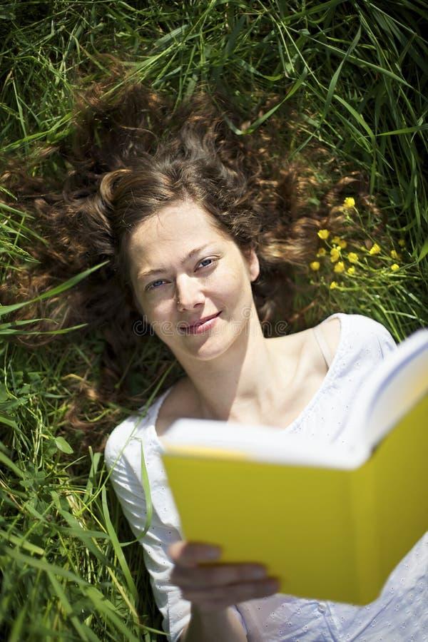 位于的草甸读取妇女 免版税库存照片