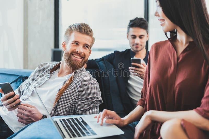 位于长沙发的愉快的微笑的工友 免版税库存照片