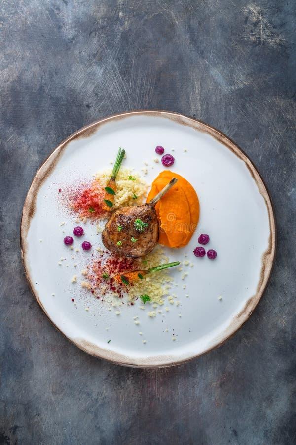 低头腿confit用batat纯汁浓汤、红萝卜和蒸丸子,餐馆膳食,拷贝空间 免版税图库摄影