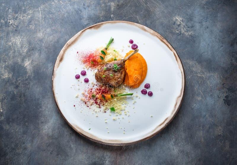 低头腿confit用batat纯汁浓汤、红萝卜和蒸丸子,餐馆膳食 免版税库存图片