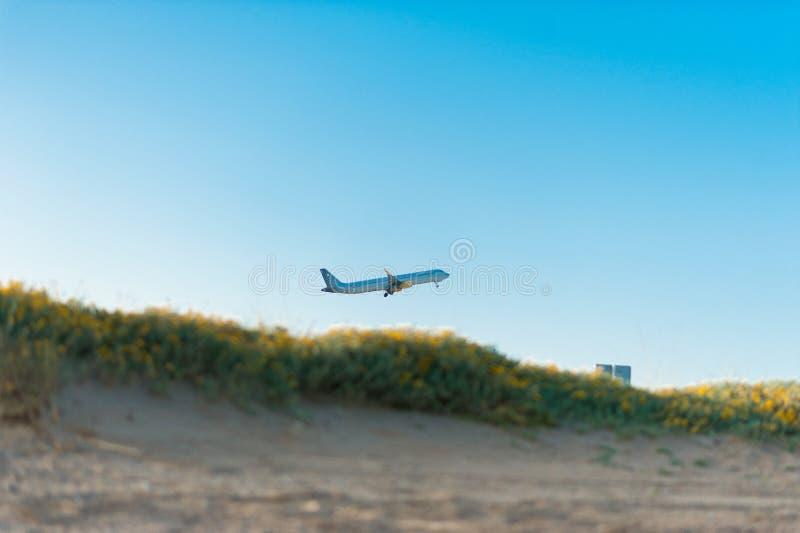 低成本航空公司飞行在从el prat机场的夏日离开在从海滩看见的巴塞罗那 库存图片