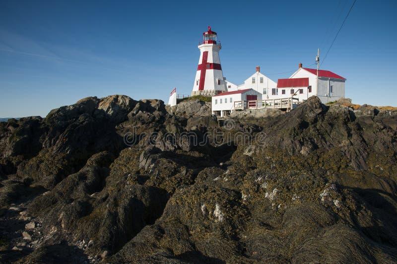 低潮显示岩石岸在顶头港口灯塔在加拿大 库存图片