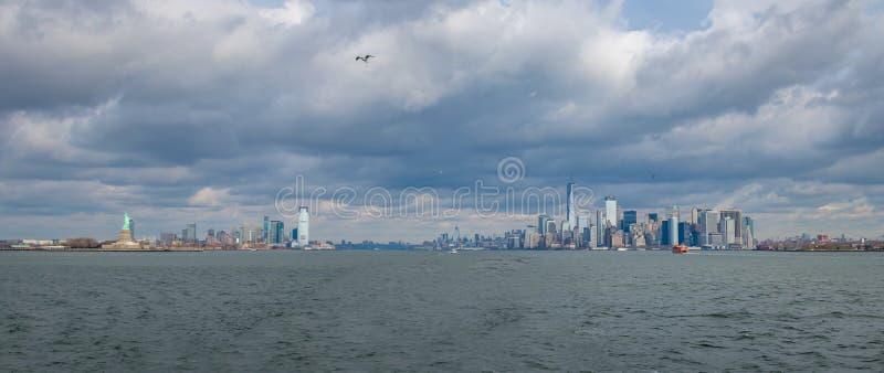 更低的曼哈顿地平线和Libery海岛和自由雕象-纽约,美国全景  免版税库存照片