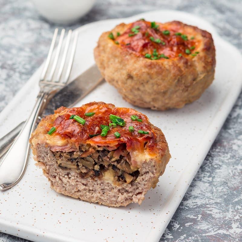 低碳paleo肉杯子,充塞用蘑菇,烟肉和乳酪,装饰与大葱,在一块白色板材,方形的格式 免版税库存照片