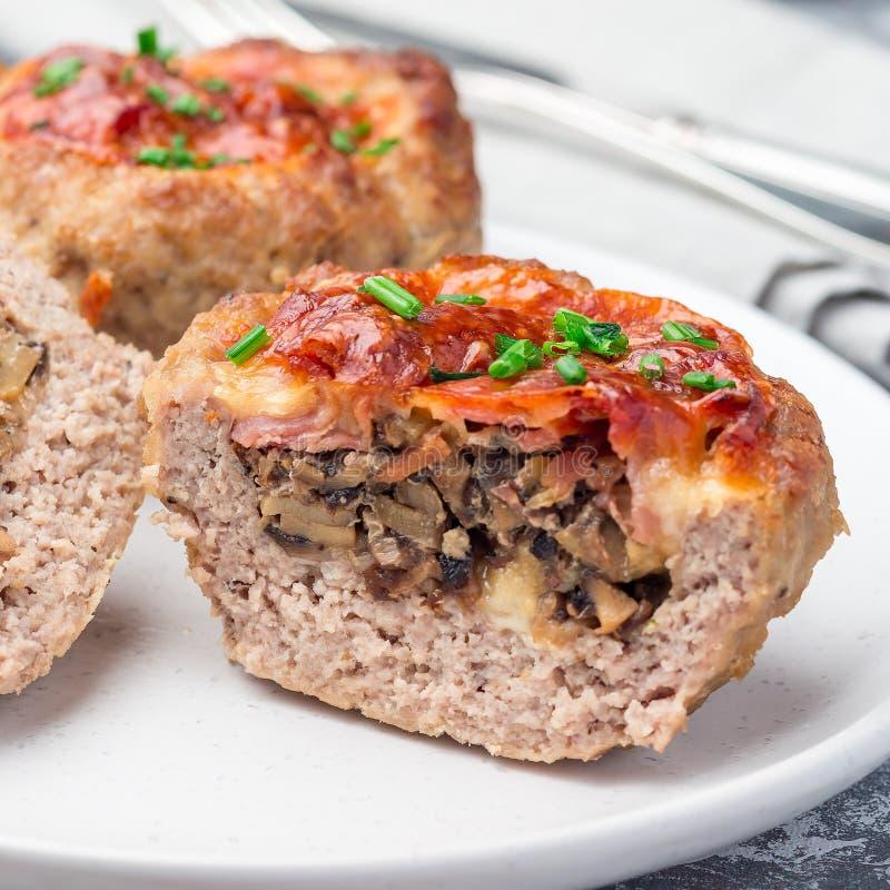 低碳paleo肉杯子,充塞用蘑菇,烟肉和乳酪,装饰与大葱,在板材,方形的格式, 免版税图库摄影