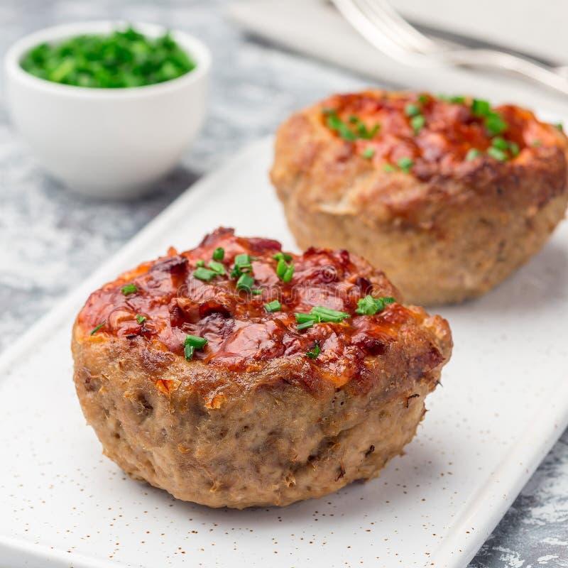 低碳paleo肉杯子,充塞用蘑菇,烟肉和乳酪,装饰与大葱,在白色板材,方形的格式 免版税库存图片