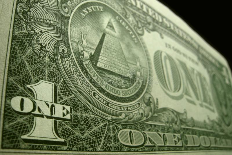 低角度关闭美国的后面一美金,集中于一个和1在左下角落 免版税库存图片