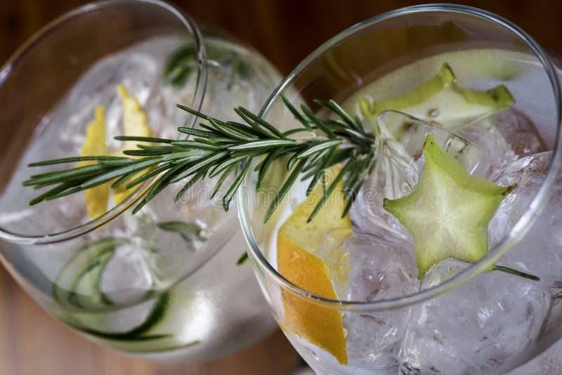 低角度关闭金汤尼苏打冰冷的现代食家工艺鸡尾酒柠檬切片和迷迭香装饰的 库存图片