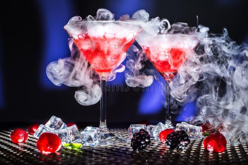 低角度现代视图点心展示或杯红色鸡尾酒和烟或干冰蒸汽,冰块莓铸造的blackberrys 免版税库存图片