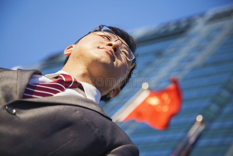 低角度观点的在一个大厦前面的年轻商人与中国旗子在背景中 库存照片