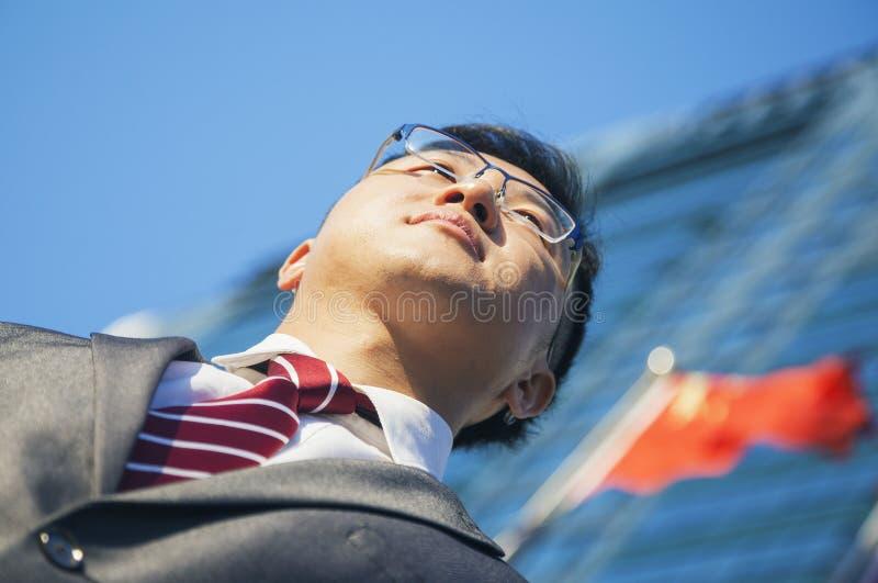低角度观点的在一个大厦前面的年轻商人与中国旗子在背景中 图库摄影