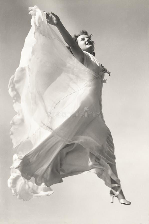 低角度观点的跳跃在空中的褂子的妇女 免版税库存照片