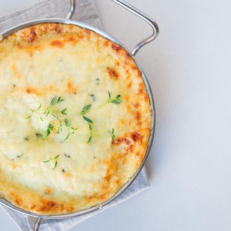 低贱加调料烘烤的土豆或土豆焦干酪在一个烘烤的盘,假日题材,方形的格式,顶视图,拷贝空间 图库摄影