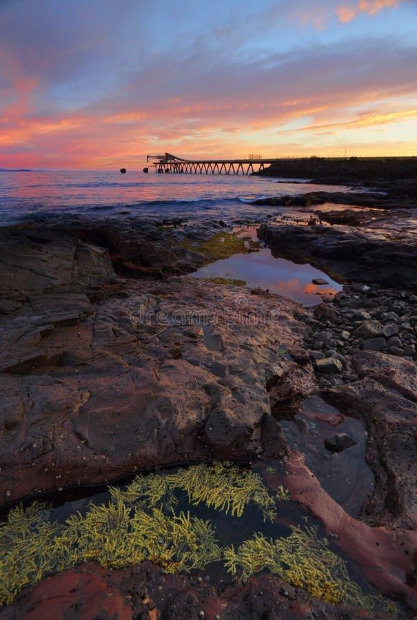 从低音点的日出与石渣在距离的装载者码头 库存照片