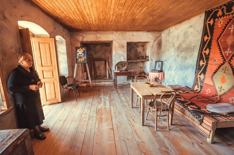 住在著名英王乔治一世至三世时期画家里面Niko Pirosmani减速火箭的样式家博物馆的资深妇女村庄 图库摄影
