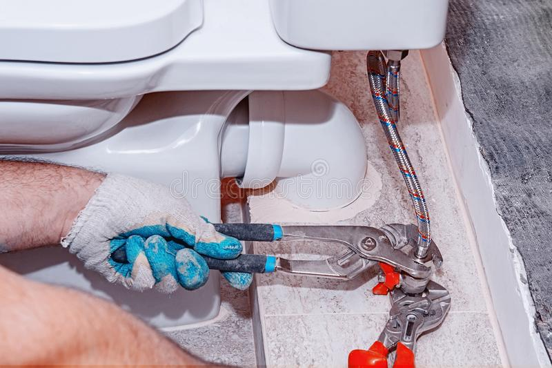 住宅修理,替换阀门阀门,配管特写镜头,手红色测量深度的钳子 测量深度的特写镜头装置 库存图片