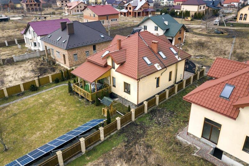 住宅区空中顶视图与新房的有屋顶太阳照片流电盘区,风轮机磨房和独立的 免版税库存图片