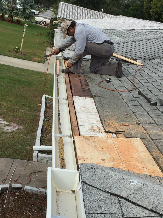 住宅屋顶、滴水边缘和天沟修理;盖屋顶的人 免版税库存图片