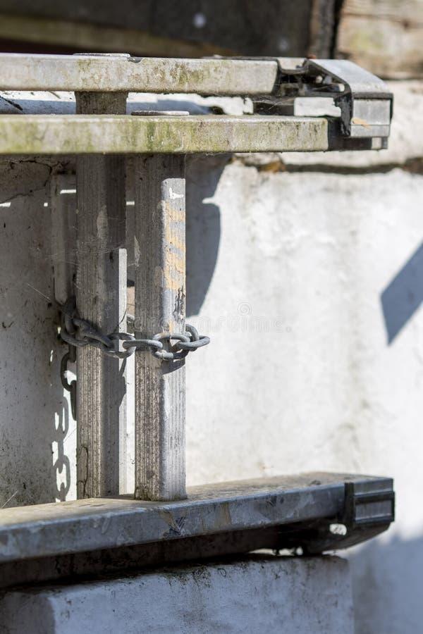 住家安全 老梯子被束缚对墙壁 库存照片