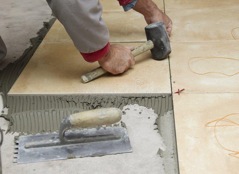 住所改善,整修-建筑工人铺磁砖工铺磁砖,陶瓷砖地板胶粘剂,有灰浆的修平刀 库存图片