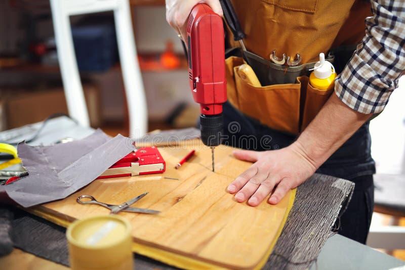 住所改善-杂物工钻木头在车间 免版税库存照片