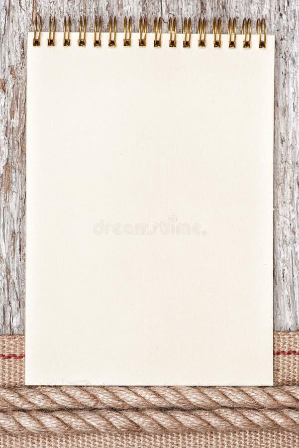 系住,纸笔记本和硬件丝带在老木头 免版税库存照片