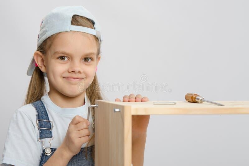 总体家具收藏家的女孩设法拧紧螺丝 免版税库存照片