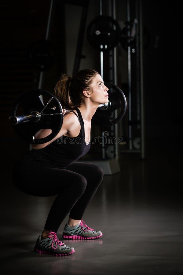 体操培训重量妇女 虔诚在健身房和做蹲坐低调照片的车身制造厂女孩举的重量 免版税库存图片