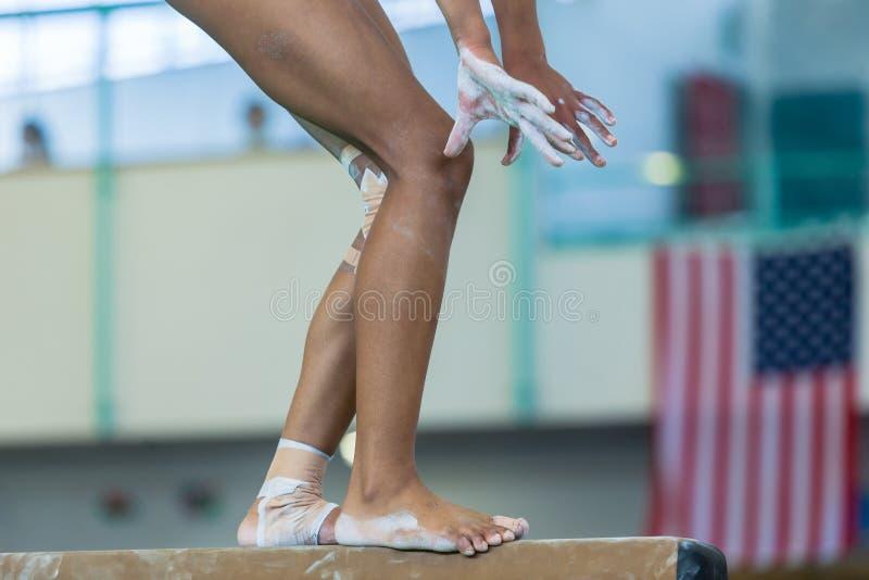 体操女孩平衡木特写镜头腿手 免版税库存照片