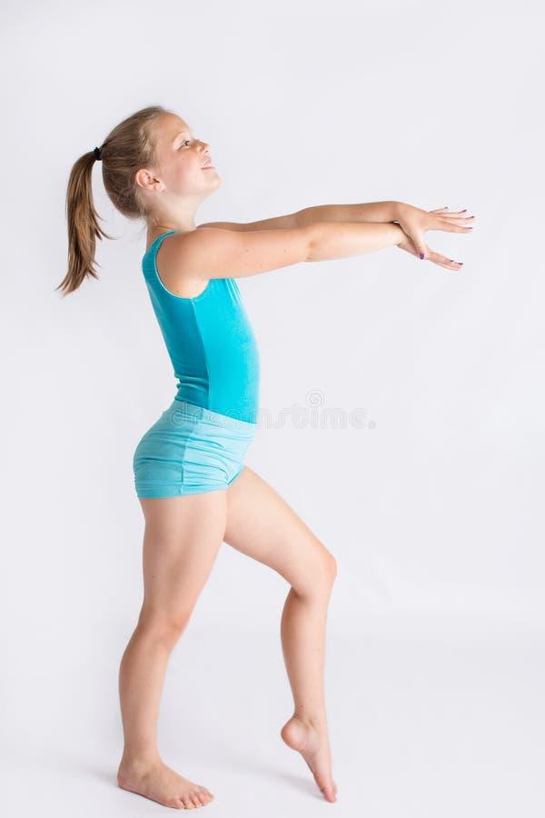 体操姿态的微笑的女孩 免版税图库摄影