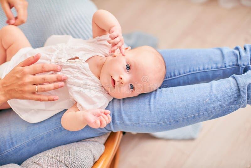 体操婴孩 做与婴孩的妇女锻炼它的发展的 按摩一小新生儿 库存图片