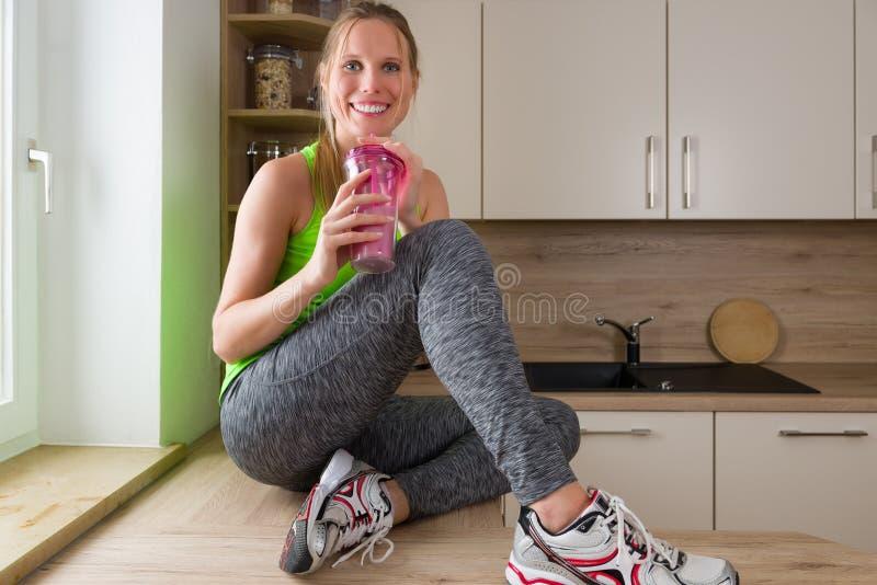 体操服饮用的蛋白质震动的白种人妇女在厨房里 免版税库存图片