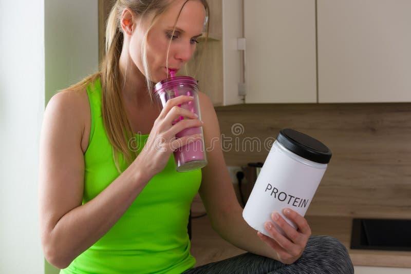 体操服饮用的蛋白质震动的白种人妇女在厨房里 库存图片