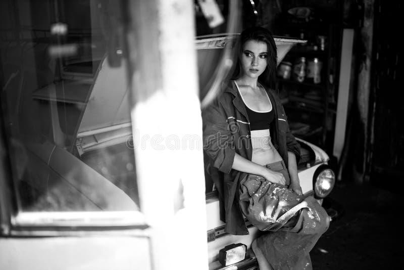 总体的女孩工作者在车间近被打开的斗蓬站立  库存照片