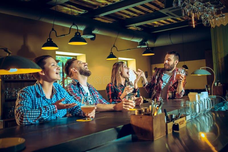 体育、人们、休闲、友谊和娱乐概念-喝啤酒的愉快的足球迷或男性朋友和 库存照片