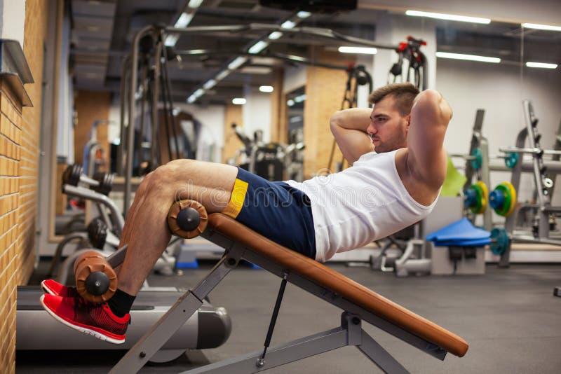 体育、健身、体型、生活方式和人概念-做仰卧起坐胃肠锻炼长凳的年轻人压入 库存图片