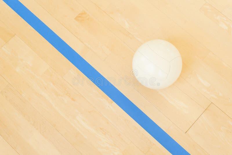 体育、健身、比赛、运动器材和对象概念-接近在木地板上的排球球从上面 免版税库存图片