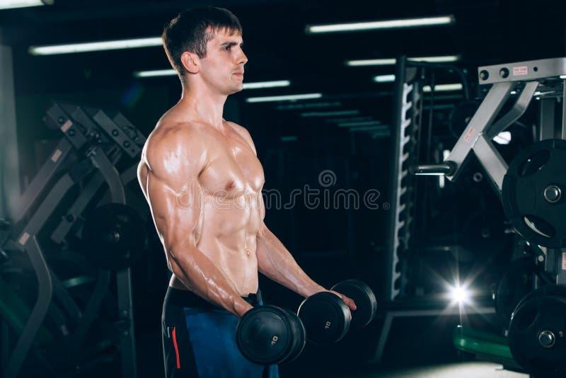 体育、健身、生活方式和人概念-做与哑铃的肌肉爱好健美者人锻炼在健身房 图库摄影