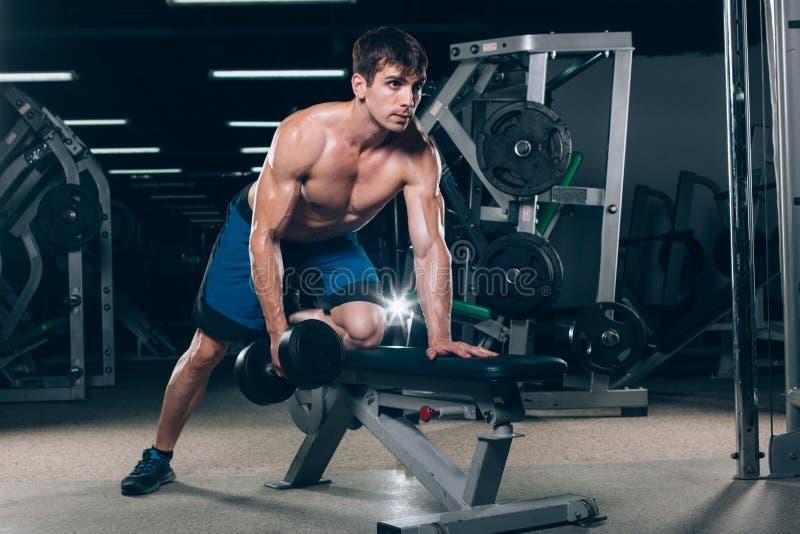 体育、健身、生活方式和人概念-屈曲有哑铃的肌肉在健身房 图库摄影
