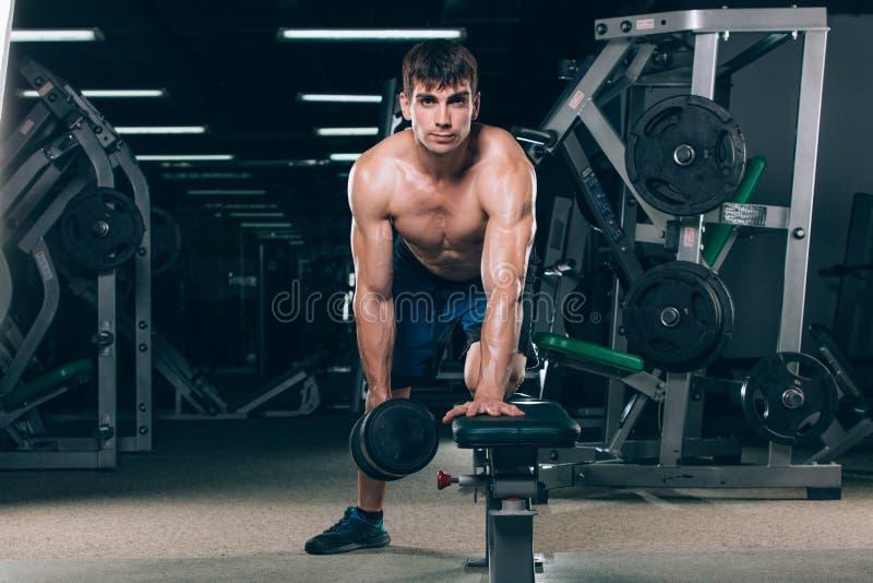 体育、健身、生活方式和人概念-屈曲有哑铃的肌肉在健身房 库存照片
