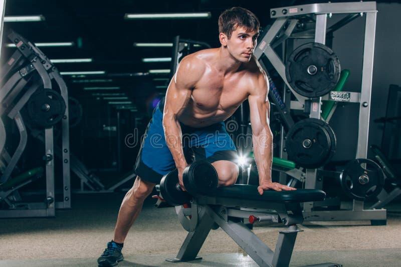 体育、健身、生活方式和人概念-屈曲有哑铃的肌肉在健身房 免版税库存图片