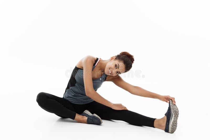 体育、训练、生活方式和健身概念-舒展腿的美丽的愉快的非裔美国人的妇女画象,当时 库存照片