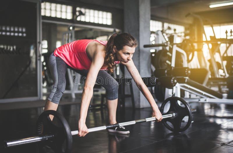 体育与杠铃的妇女锻炼,女性在运动服做锻炼在健身房 库存图片