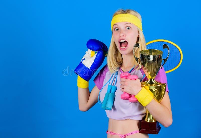 体育为每天 体育商店分类 女孩成功的现代妇女举行金黄觚体育冠军和 免版税库存图片