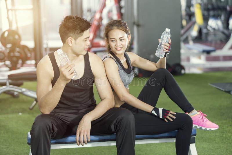 体育人和妇女饮用水在锻炼以后在健身房 免版税图库摄影